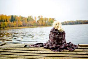 Посидіти на природі біля озера з чашкою чаю, загорнувшись у плед